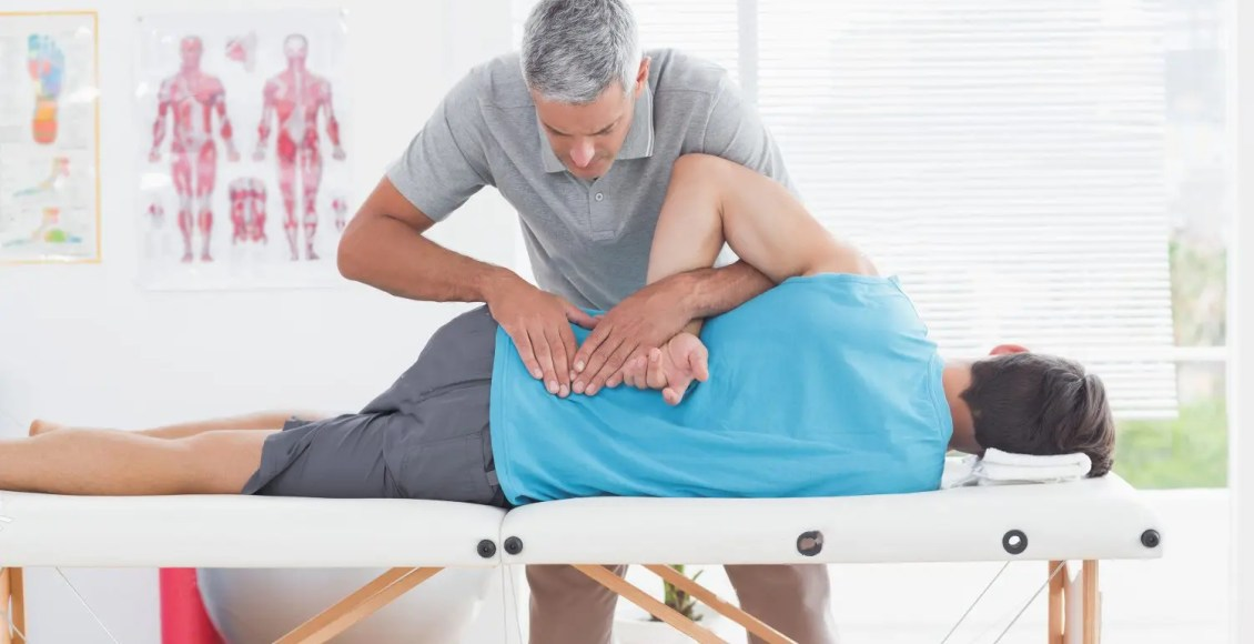 stock photo doctor examining man back in medical office