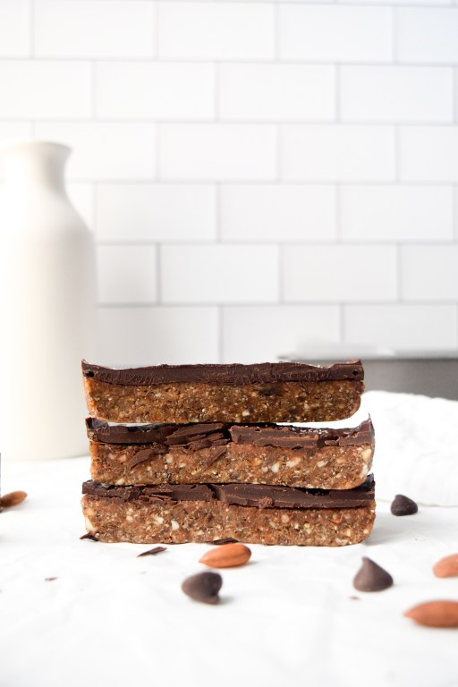 a stack of dark chocolate almond date bars with a white background and pieces of almonds and chocolate chips sprinkled throughout