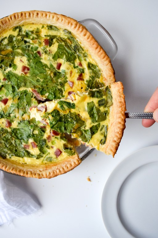 A slice of quiche focused above a pie plate of quiche.