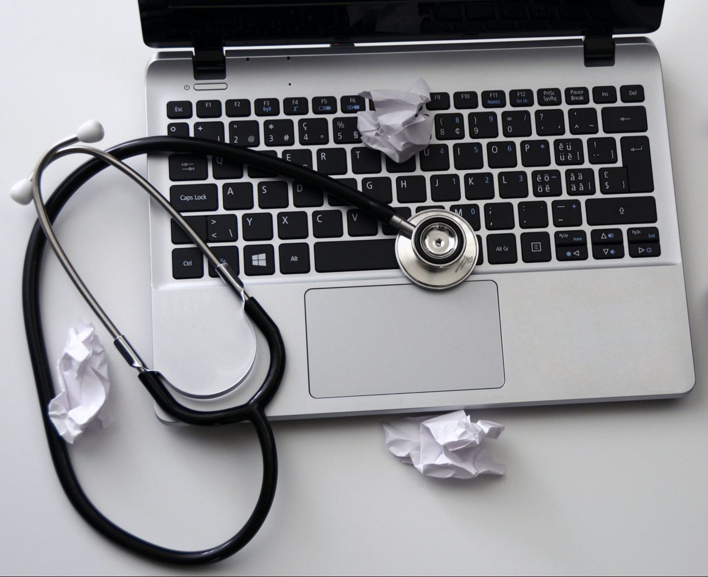 Computer, stethoscope, and many crumpled pieces of paper. Image depicts the struggle of developing and implementing wellness programs for healthcare providers.