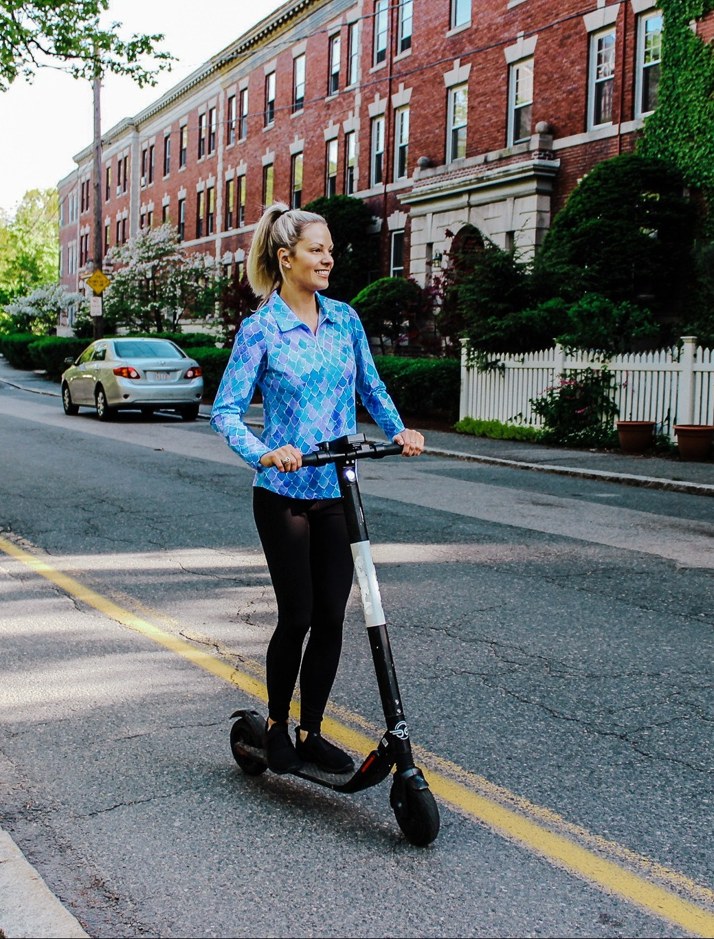 Blonde woman on electric scooter.
