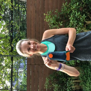 Girl in green sports bra and grey tank top outdoors, holding a running insole and flexing to show its pliability.
