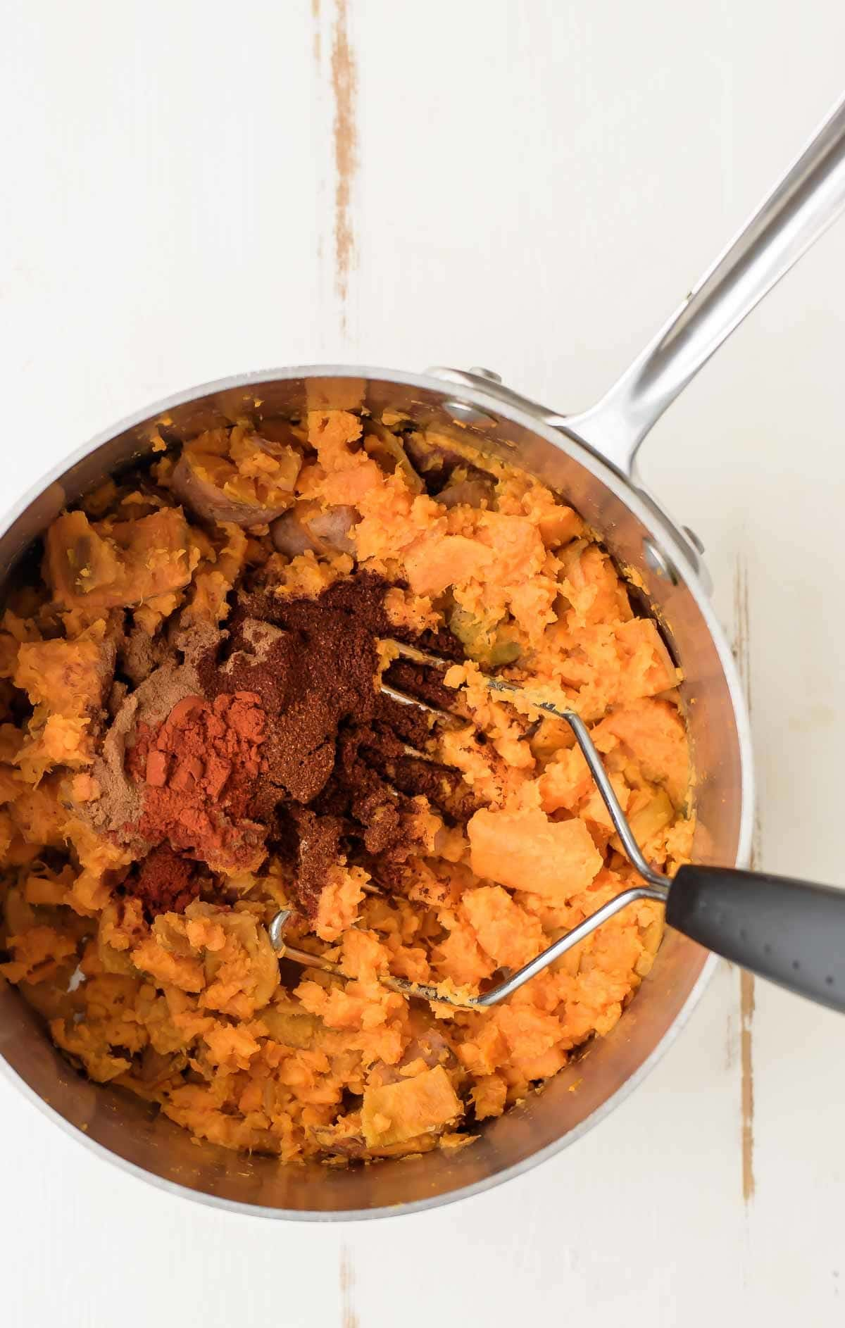 mashing sweet potatoes with spices to make vegan sweet potato quesadillas