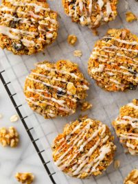 Healthy Carrot Cookies with Orange Icing. These soft and chewy cookies are FLOURLESS, vegan, gluten free, and naturally sweetened! Super easy recipe with oatmeal, cinnamon, and any of your other favorite carrot cake mix-ins. Simple, kid friendly and good enough to eat for breakfast!