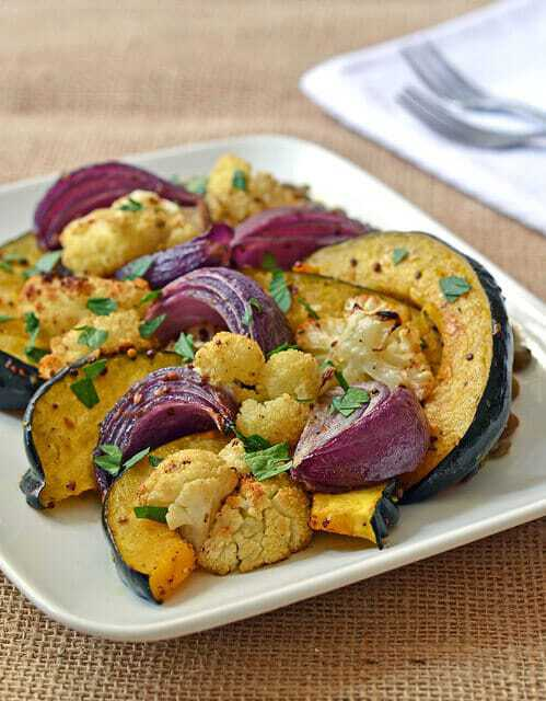 The best oven roasted vegetables ever for a crowd served on a plate with lentils