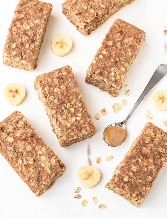 Peanut Butter Oatmeal Breakfast Bars surrounded by slices of banana and a spoonful of peanut butter