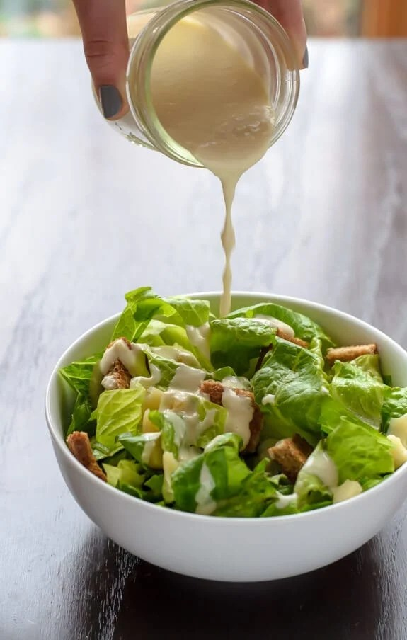 Homemade Caesar dressing no mayo poured over a bowl with lettuce and croutons