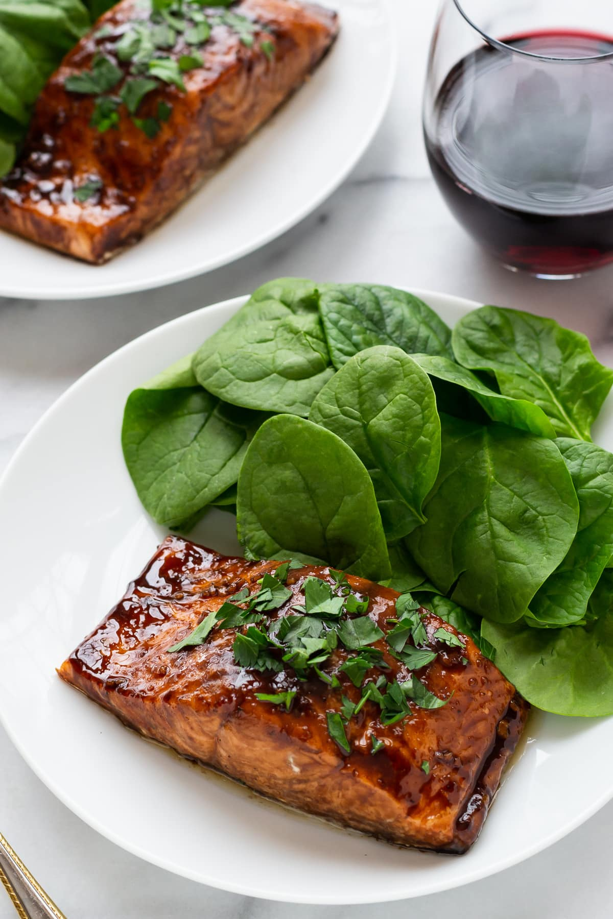 2 dinner plates of Balsamic Glazed Salmon with spinach