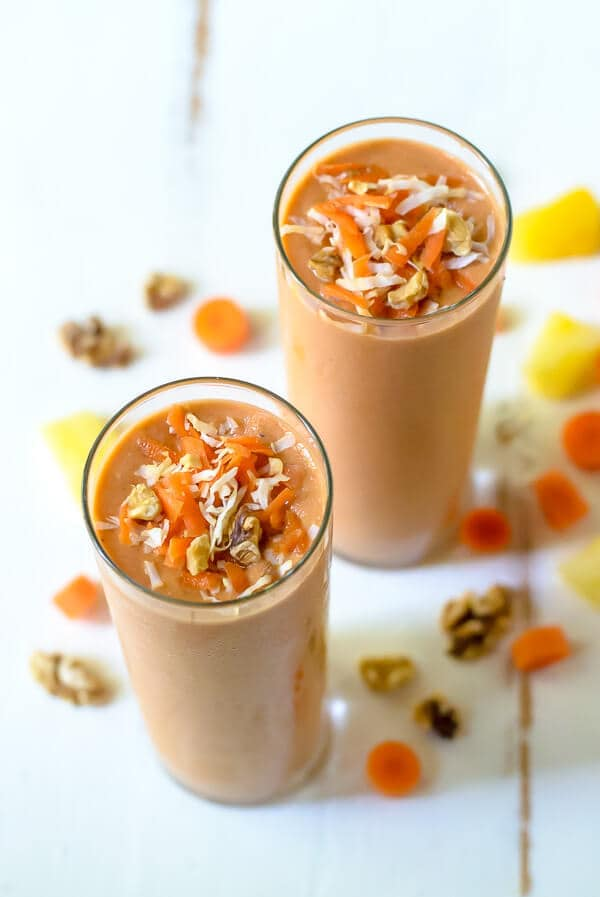 2 tall glasses of carrot cake smoothies garnished with grated carrots and coconut flakes