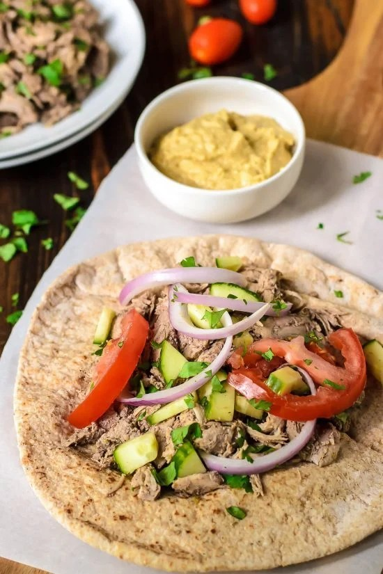 pita bread topped with Slow Cooker Chicken Shawarma, red onion, cucumber, and tomatoes