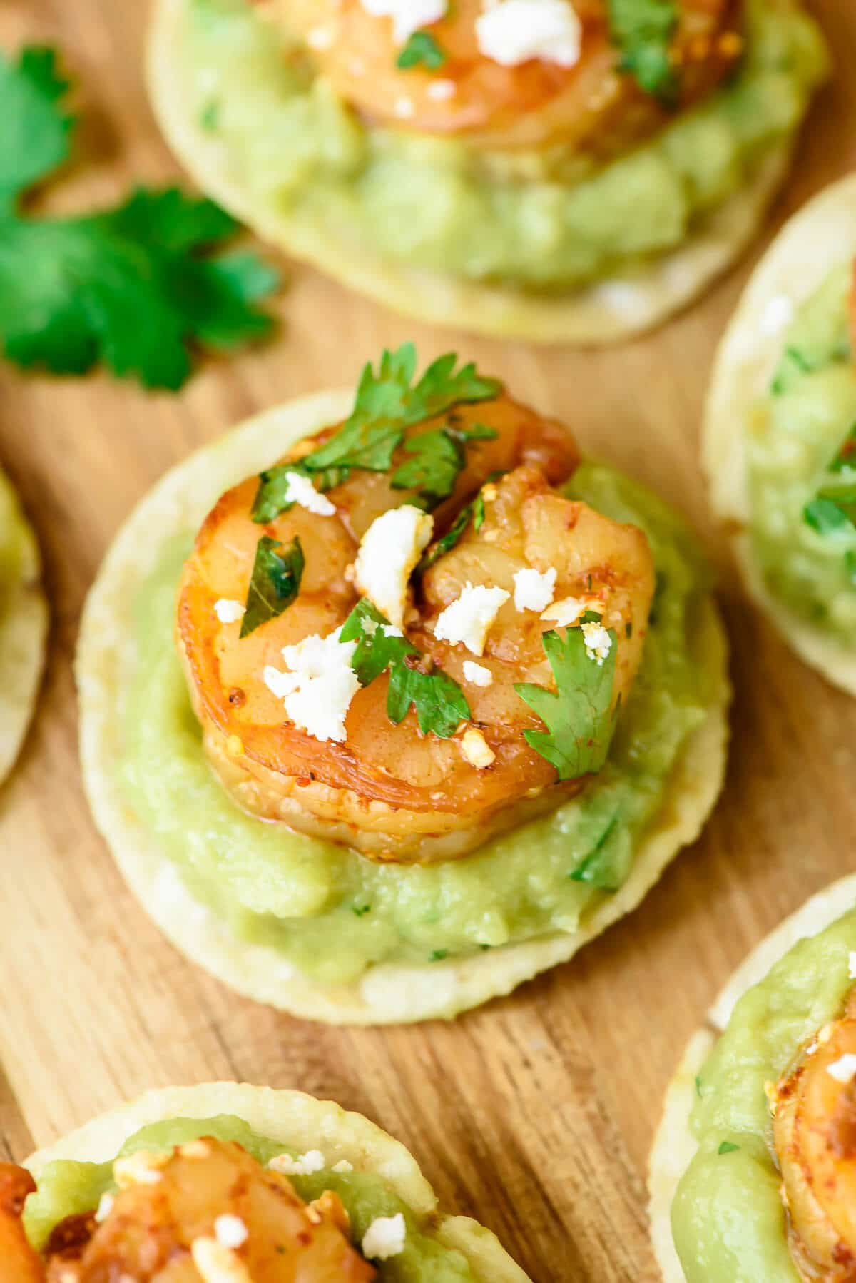 Spicy Shrimp Guacamole Bites - Juicy shrimp and spicy guacamole on top of a crunchy tortilla chip. So EASY and everyone loves this football food!