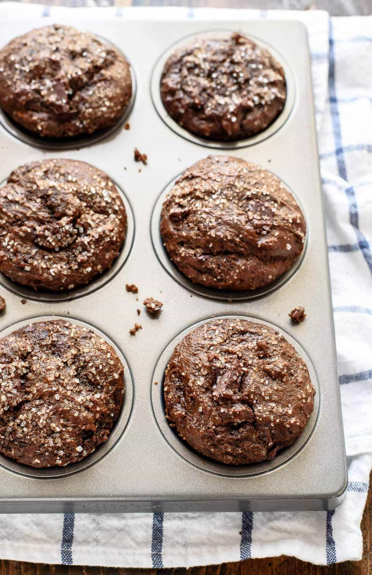 Fluffy gingerbread muffins filled with spices and chocolate! You'll never believe this recipe is healthy. Made with coconut oil, greek yogurt, and lots of spices.