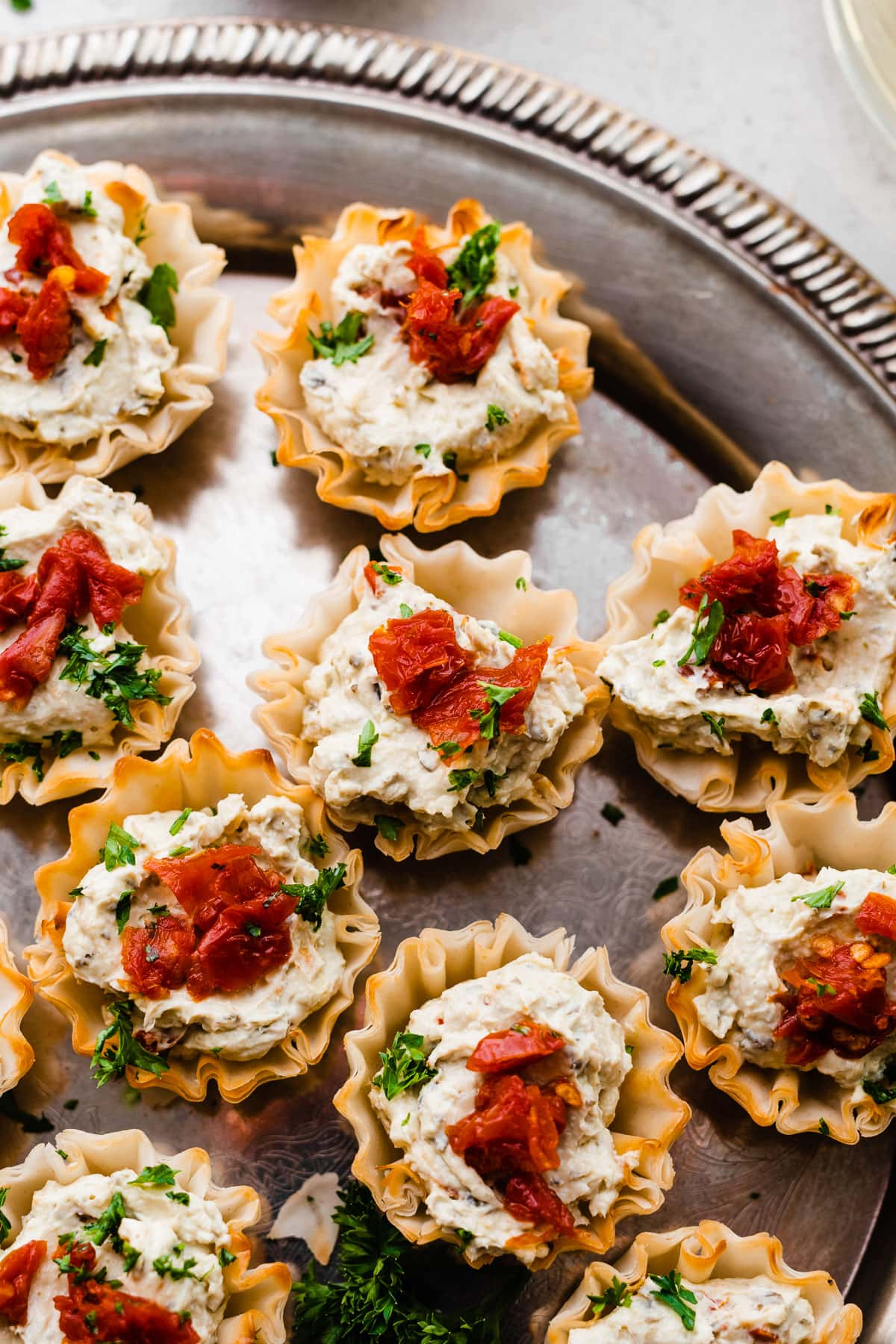 Our favorite easy appetizer: Sun Dried Tomato Pesto Bites. Creamy cheese and pesto filling with sun dried tomatoes on top.
