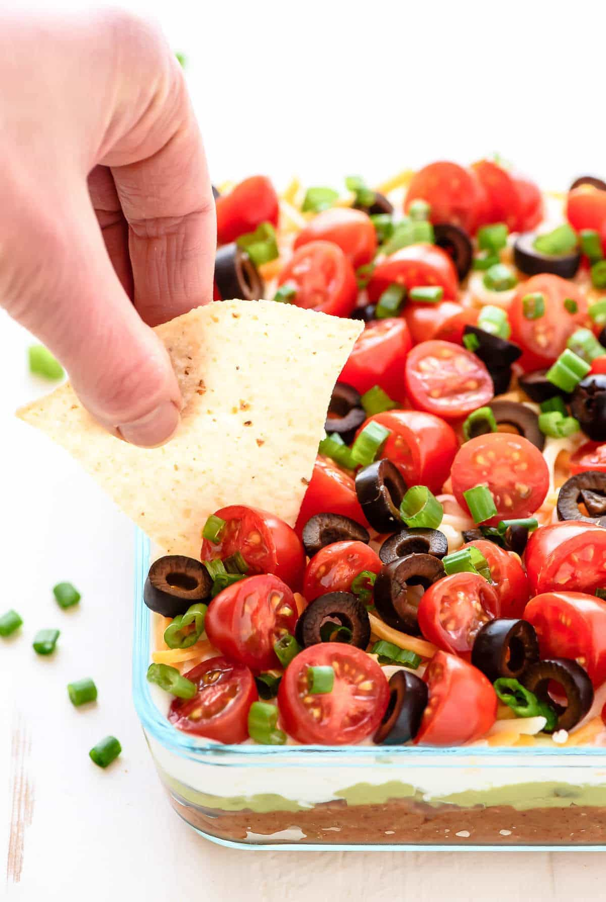 Learn how to make Classic 7-Layer Taco Dip with this simple recipe. Made with fresh ingredients, this is the BEST Mexican layer dip and is perfect for any party! www.wellplated.com
