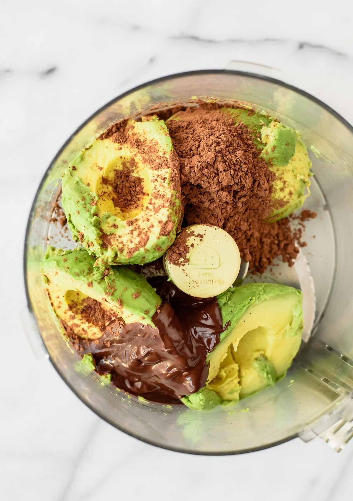 fresh avocado and cocoa powder in the bowl of a food processor