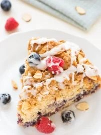 Crumb Cake recipe - this is my FAVORITE coffee cake! It has tons of buttery crumbs and the cake is so soft and moist. Loaded with fresh berries and topped with sweet vanilla glaze. @wellplated