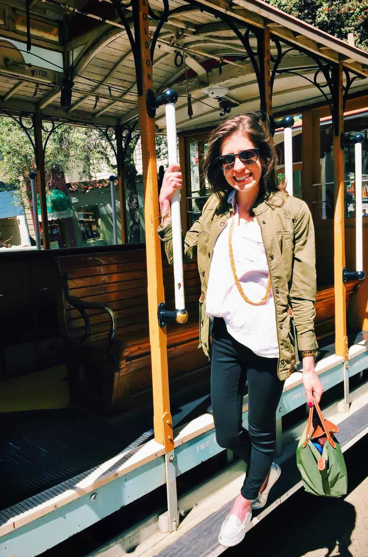 woman with long brown hair, wearing sunglasses, standing on a trolley car