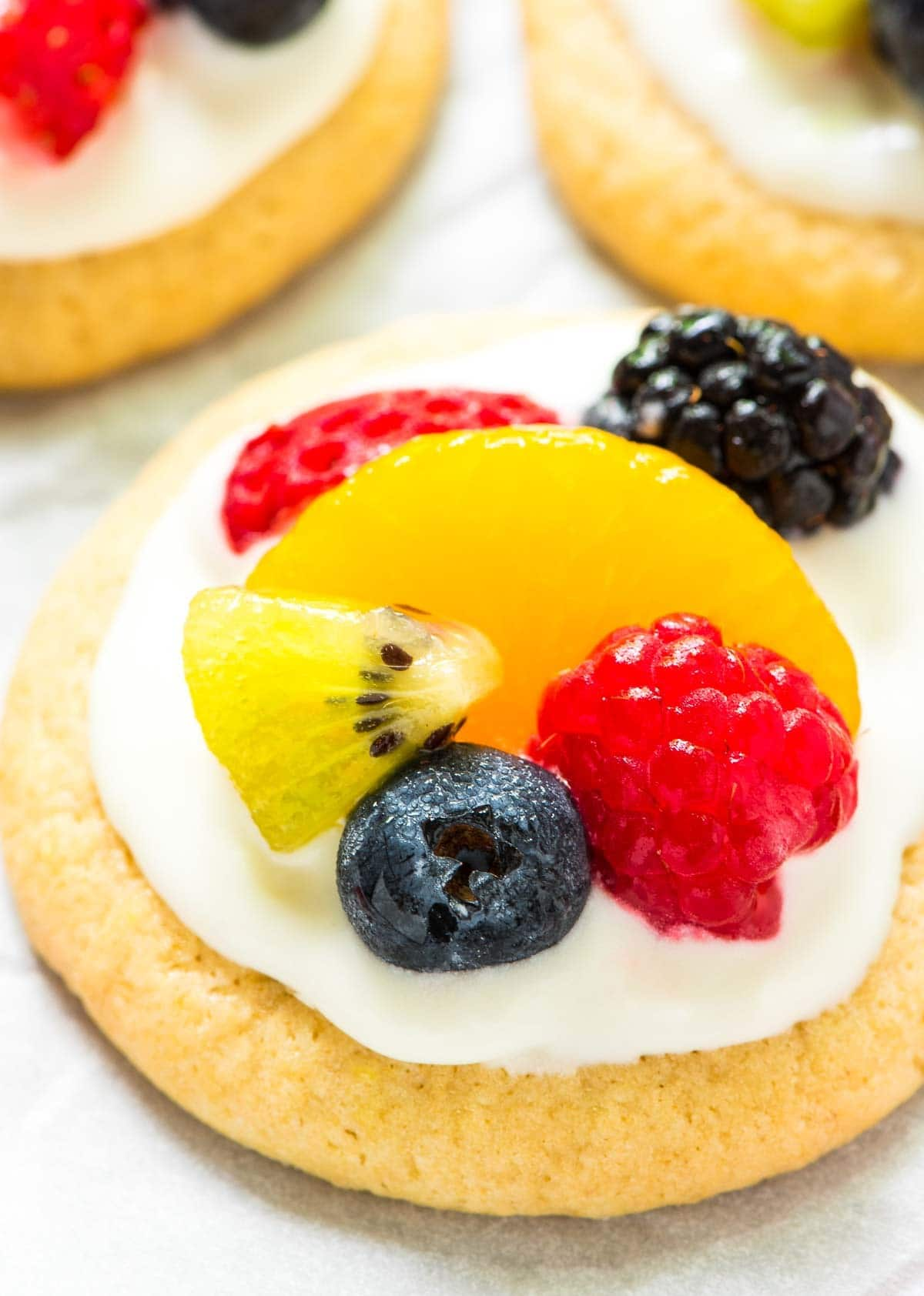 Mini Fruit Pizza Cookies. Such a cute twist on a classic summer dessert! Buttery soft sugar cookies topped with sweet cream cheese frosting and fresh fruit. Simple and delicious! @wellplated