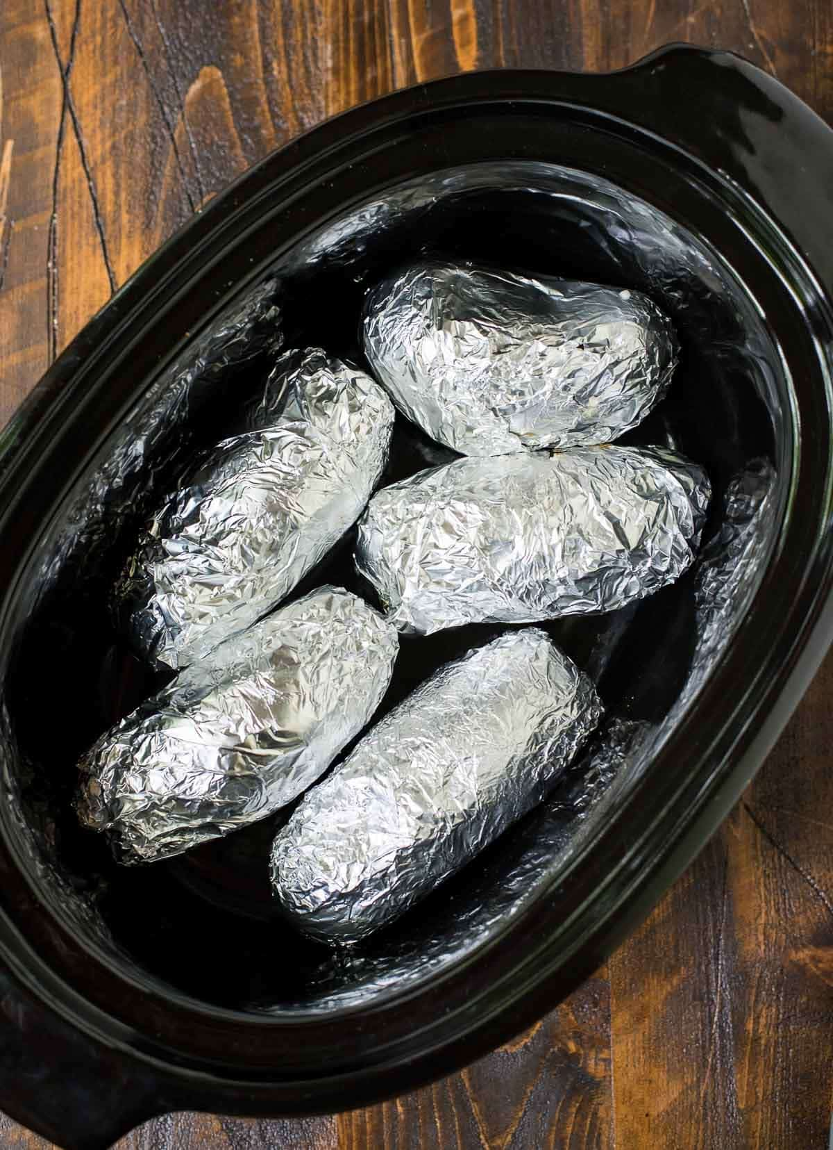 foil wrapped baking potatoes in a crock pot