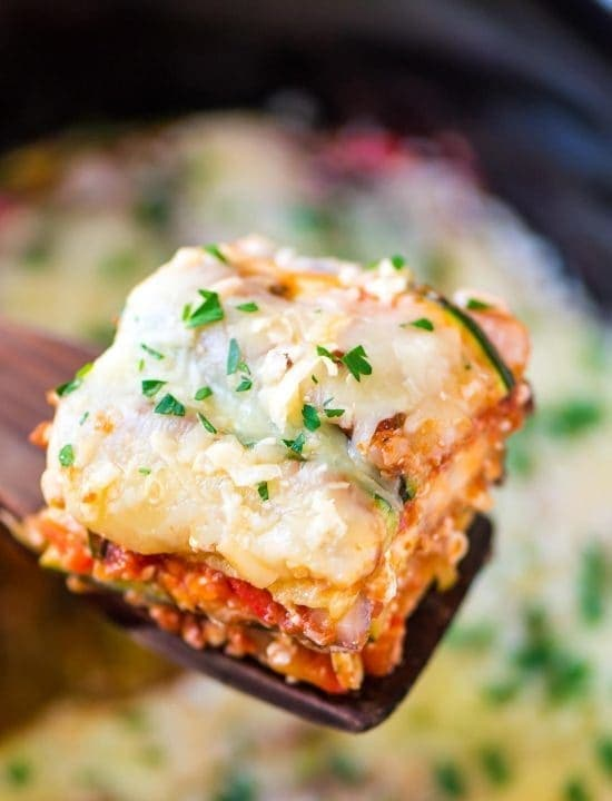 spatula holding a low carb slice of crock pot lasagna made with zucchini