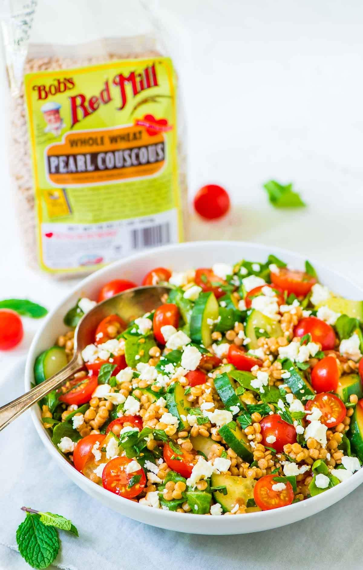 Tomato, Cucumber, and Feta Pearl Couscous Salad in a white bowl, with a bag of Bob's Red Mill pearl couscous behind it