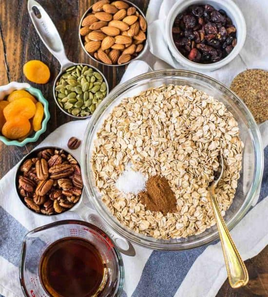 bowls of rolled oats, nuts, seeds, dried fruits and other ingredients needed to make healthy granola