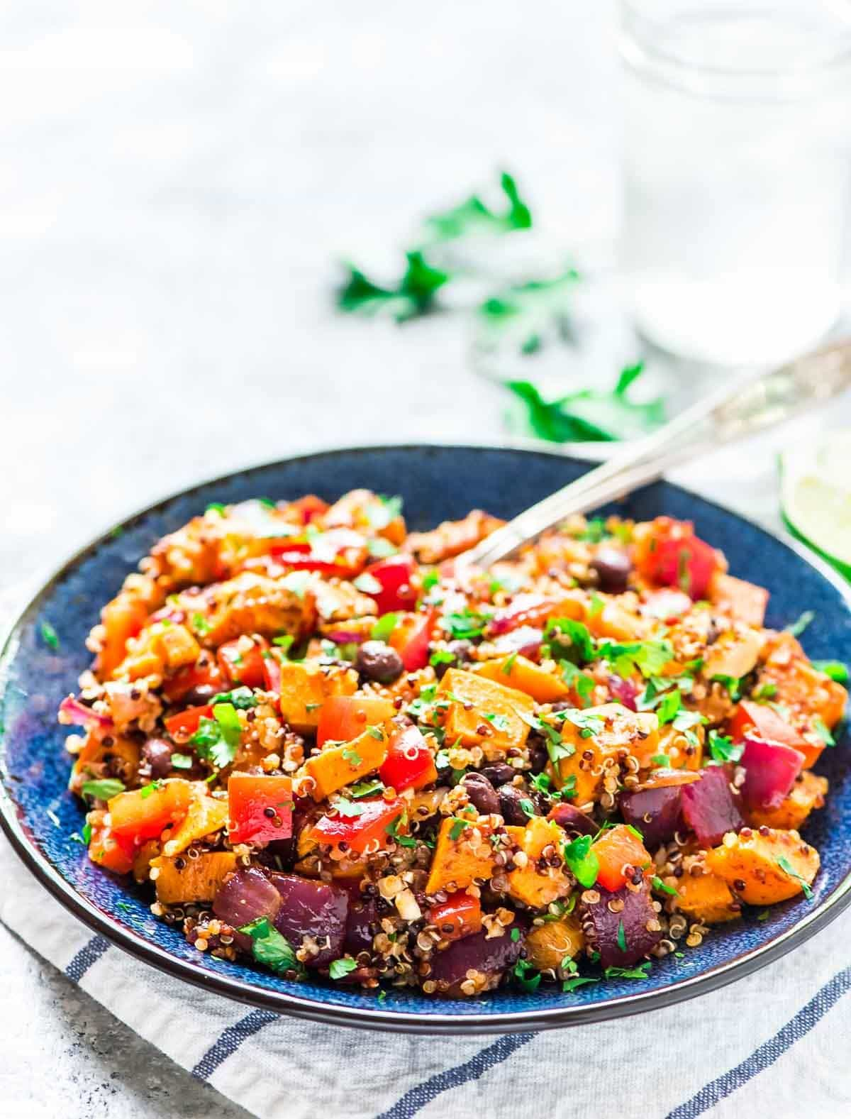 blue serving bowl filled with Black Bean Sweet Potato Quinoa Salad