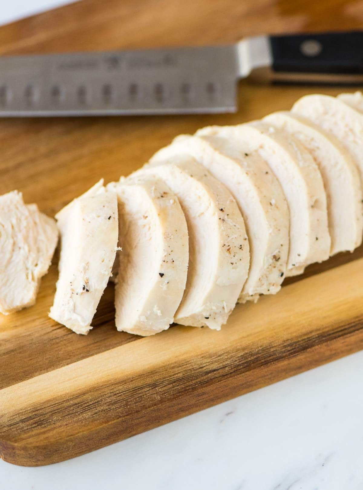 cutting board with sliced cooked chicken breast