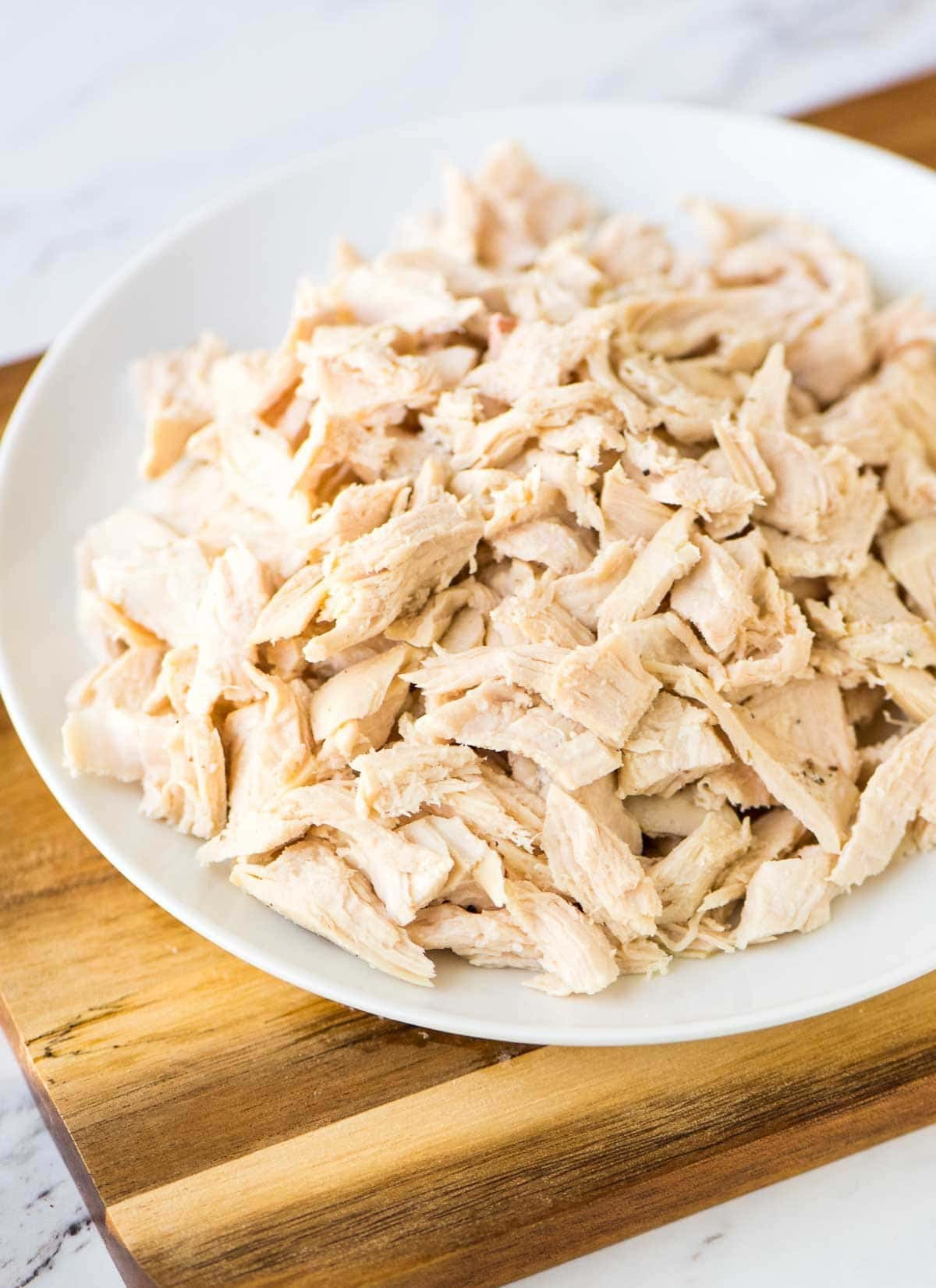 white platter of shredded chicken breast