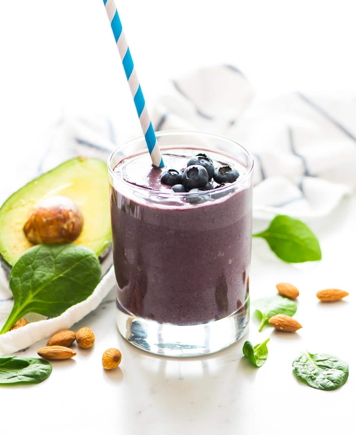 Blueberry Avocado Banana Smoothie in a glass, surrounded by some of the ingredients needed to make it