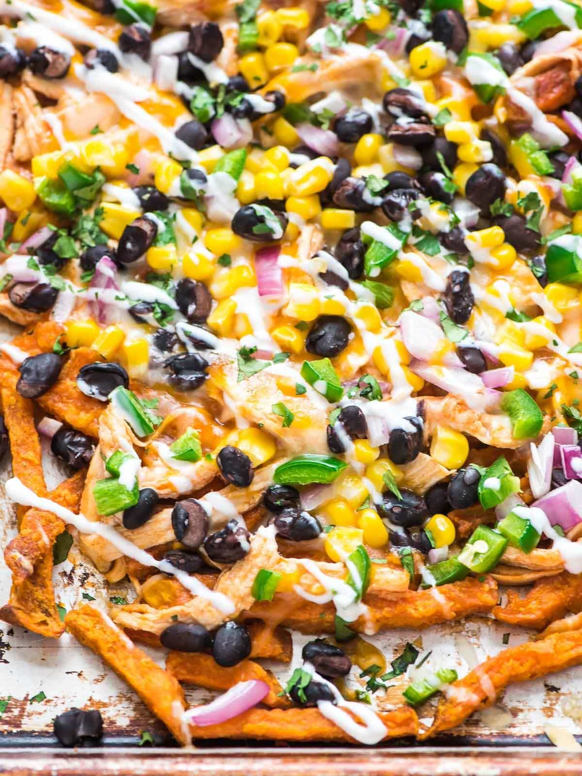 Cheesy Chicken Enchilada Sweet Potato Fries. Frozen baked sweet potato fries topped with chicken, enchilada sauce, CHEESE, black beans, and more! An easy party appetizer recipe that's perfect for football watches, game day, and tailgates. Recipe at wellplated.com | @wellplated