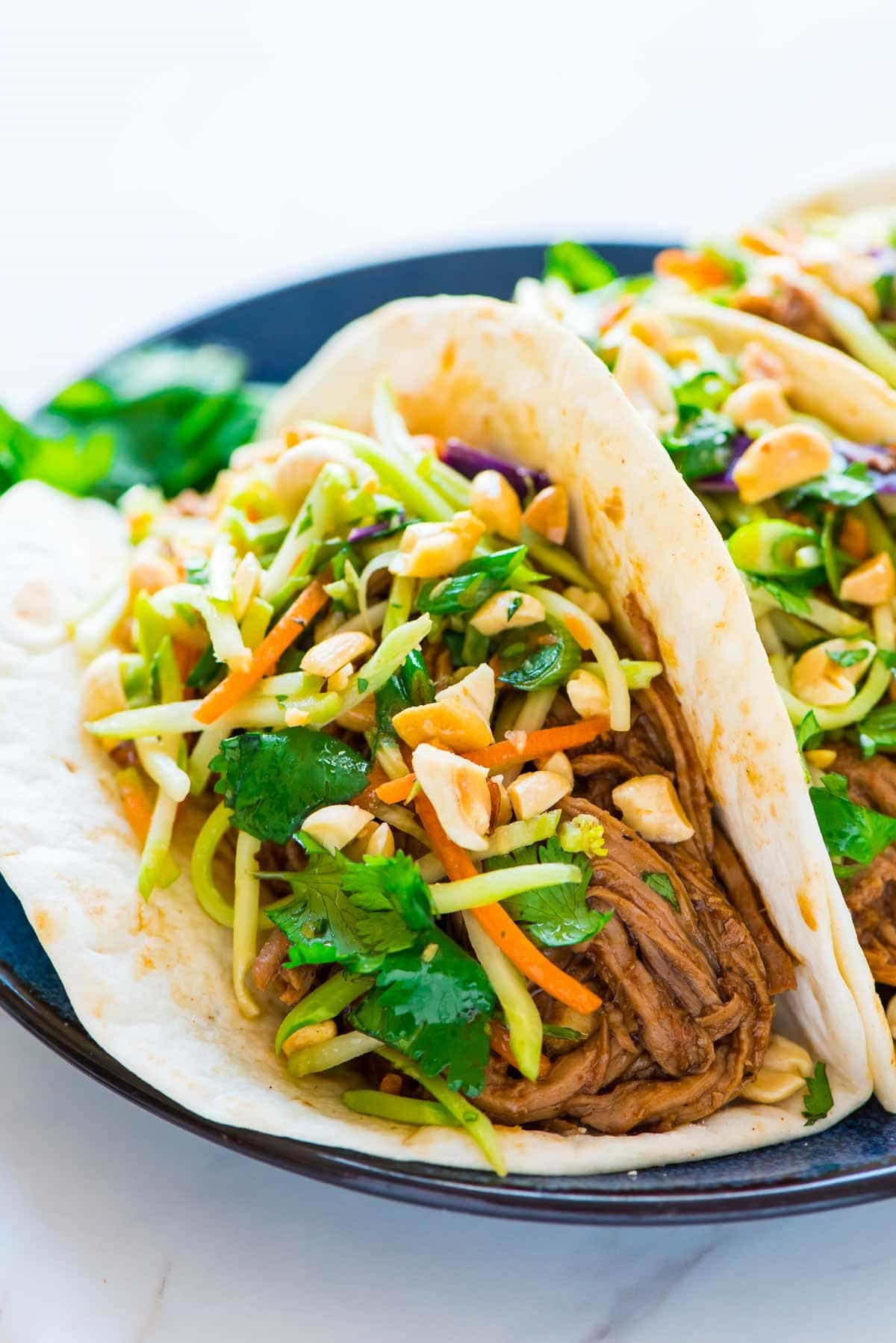 Asian pulled pork tacos topped with broccoli slaw and crunchy peanuts