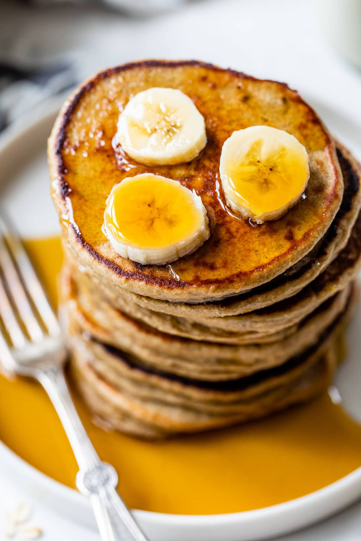 heart shaped banana oatmeal pancakes topped with sliced strawberries and bananas