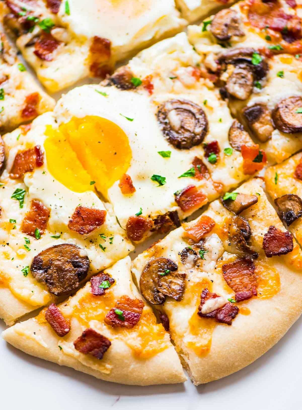 Carbonara Pizza – Garlic, crispy bacon, and creamy sunny-side up eggs. Everything you love about carbonara pasta, turned into a delicious homemade pizza! Recipe at wellplated.com | @wellplated