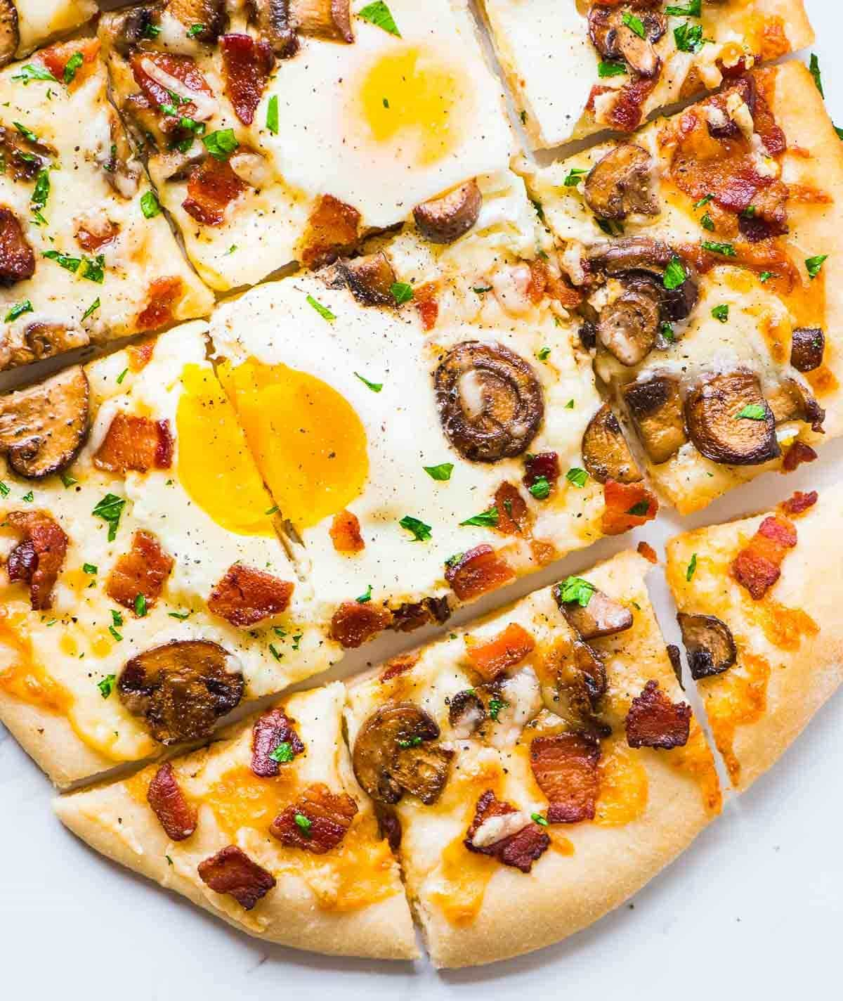 Carbonara Pizza – Crispy bacon, garlic, cream, and sunny side up eggs on a fluffy homemade pizza crust. Recipe at wellplated.com | @wellplated