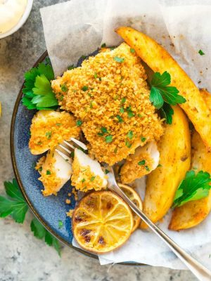 """overhead photo of a blue plate of oven baked fish with a panko crust and oven baked """"chips"""""""