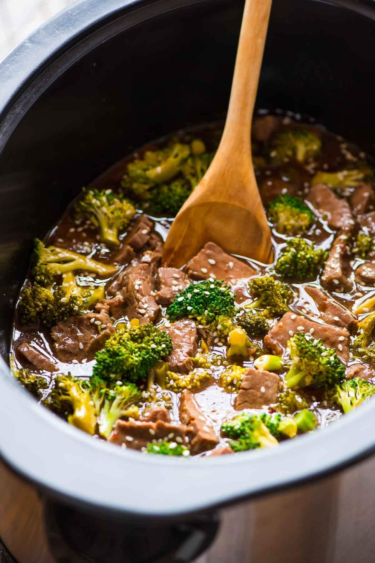 crock pot full of Asian Beef with Broccoli. A wooden spoon is stirring the dish.