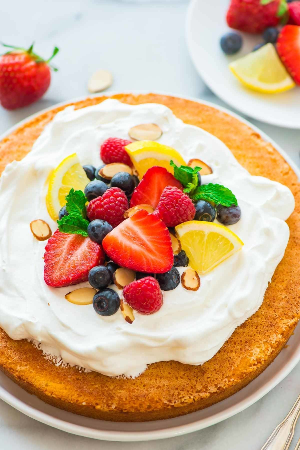 Flourless Lemon Almond Cake with Fresh Berries – a light, fluffy, and gluten free dessert made with almond flour, eggs, and sugar. Simple, low carb, and perfect for any holiday or party! Recipe at wellplated.com | @wellplated