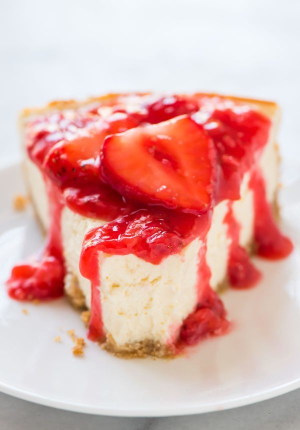 slice of Lemon Yogurt Cheesecake with Strawberry Sauce with a bite taken out of it