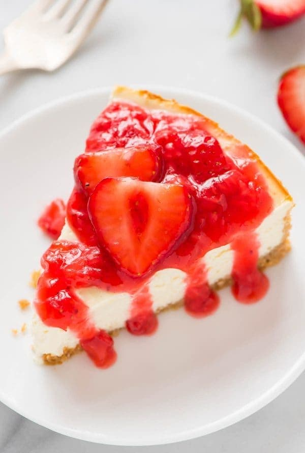 white dessert plate with a slice of Greek yogurt cheesecake topped with fresh strawberry sauce