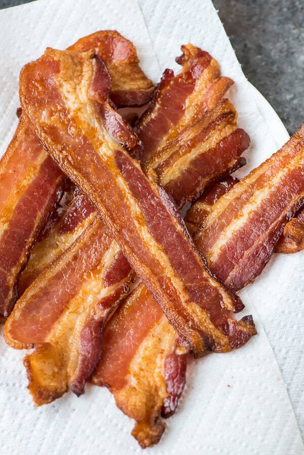 Paper towels topped with slices of crispy oven baked bacon