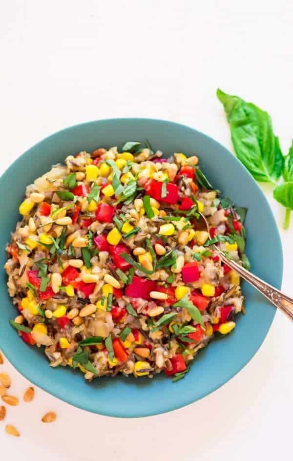 wild rice pilaf with sweet corn and bell pepper in a serving bowl with a serving spoon