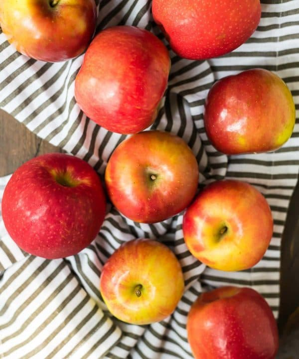 fresh Gala apples on a striped dish towel