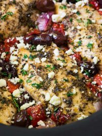 slow cooker Greek chicken topped with kalamata olives, fresh herbs, and feta cheese