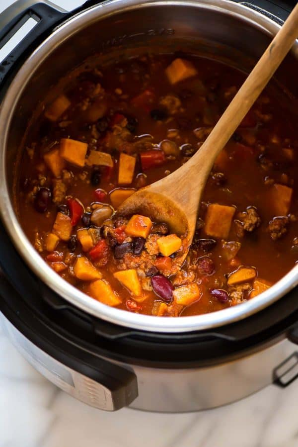 electric pressure cooker chili with a wooden spoon sitting in it.