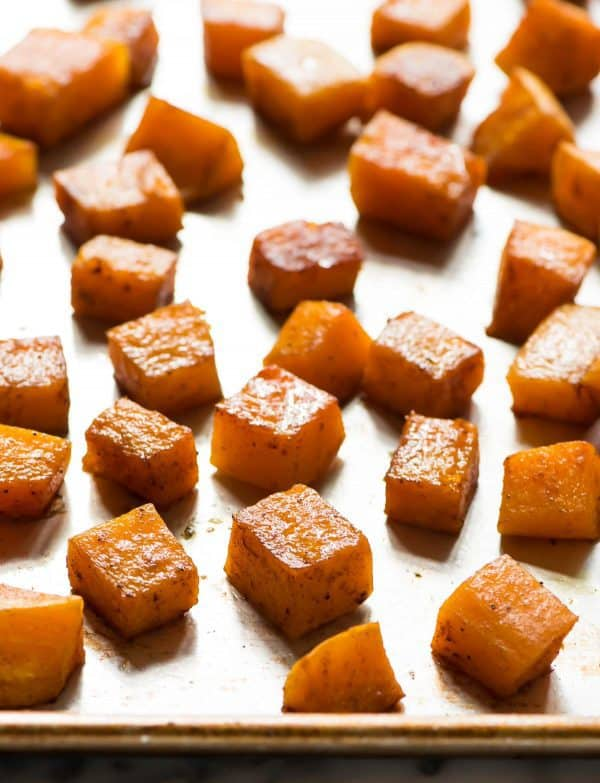 Roasted maple butternut squash cubes with cinnamon on a baking sheet