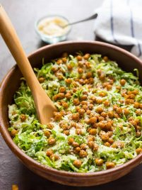 Caesar Shaved Brussel Sprout Salad with Roasted Chickpea Croutons. Perfect for healthy lunches or a holiday side dish. Made with shredded brussels sprouts, crispy roasted chickpeas, and creamy Caesar dressing. Easy and low carb!