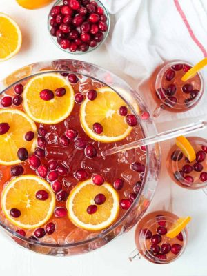 Easy, refreshing, DELICIOUS Sparkling Christmas Punch for a crowd! With champagne, rum, cranberry, and apple cider. Not to sweet, spiked, and so red and festive! Recipe includes nonalcoholic option.