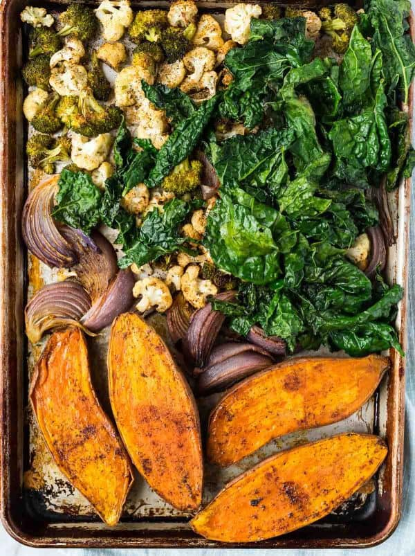 A sheet pan with sweet potatoes, onions, cauliflower, broccoli, and kale for making vegetarian power bowl recipes