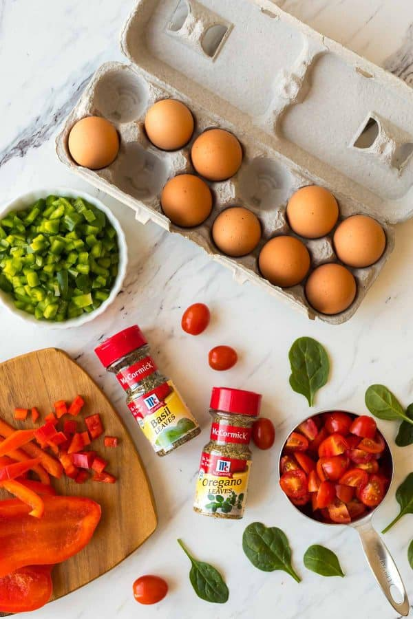 A carton of eggs, chopped vegetables, and spices for making breakfast